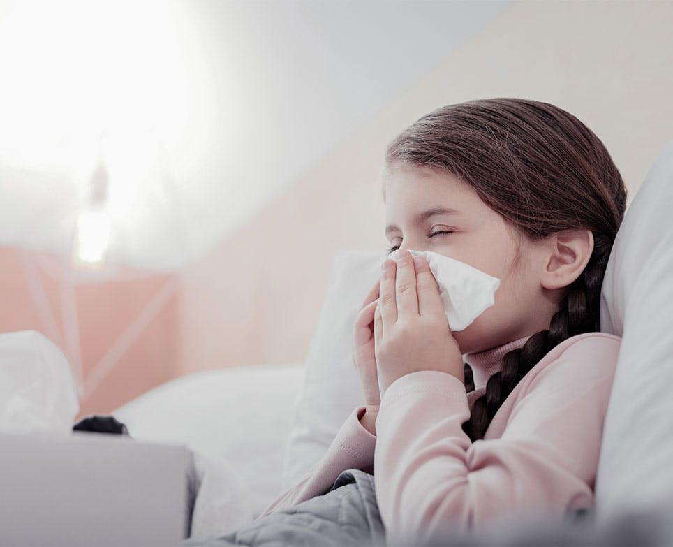 Niña se limpia la nariz con un pañuelo.