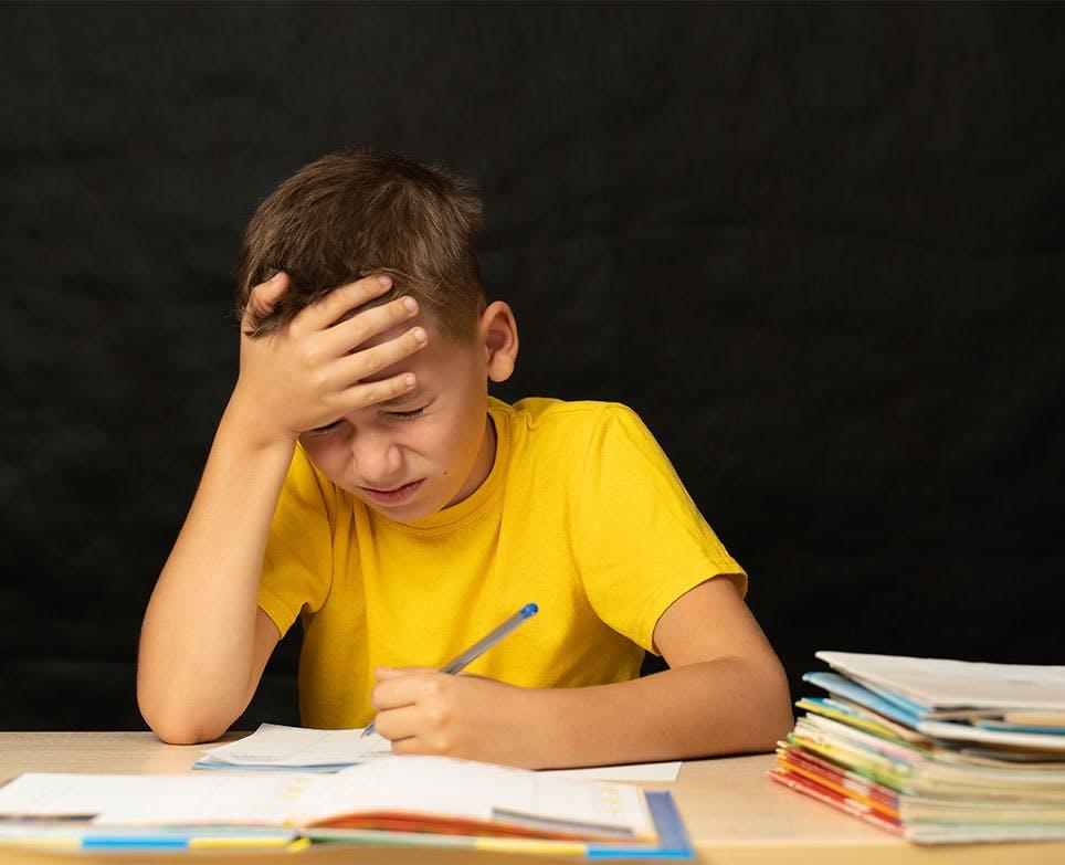 Niño se toma la cabeza en señal de dolor mientras estudia.