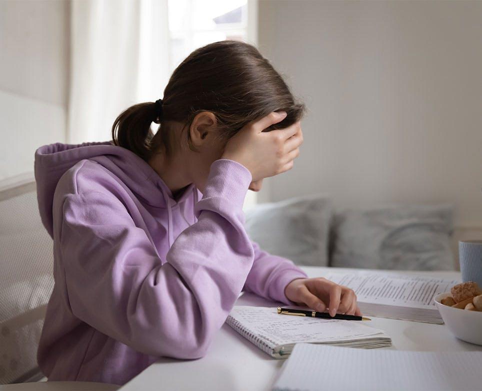 Niña estudiando mientras se toca la cabeza en señal de dolor.