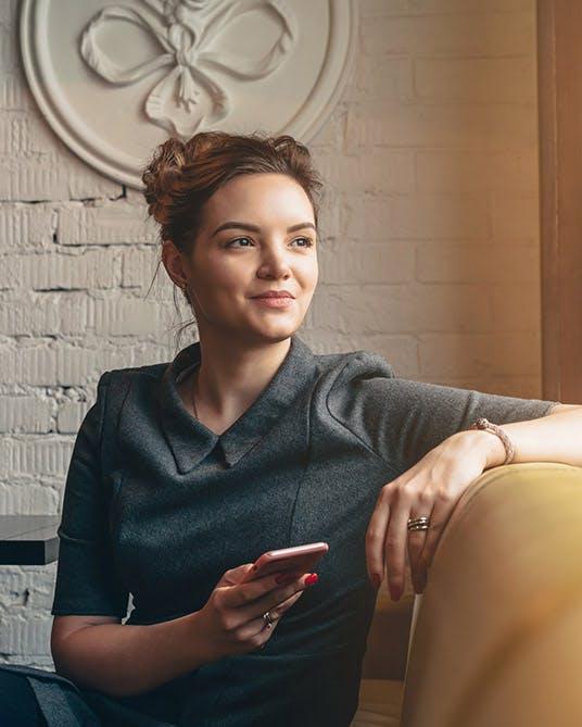 Mujer sentada en un mueble con su celular en la mano.