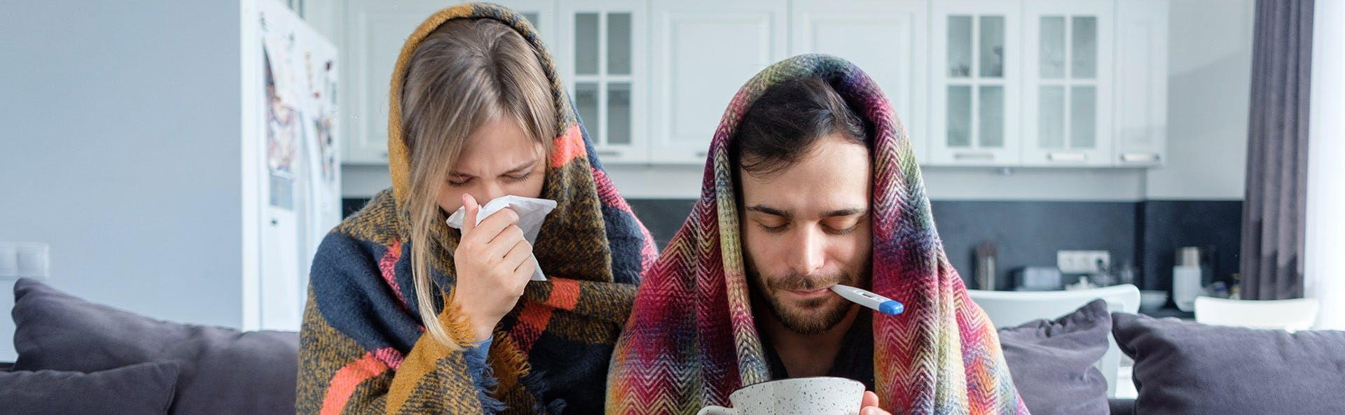 Pareja de hombre y mujer con síntomas gripales.