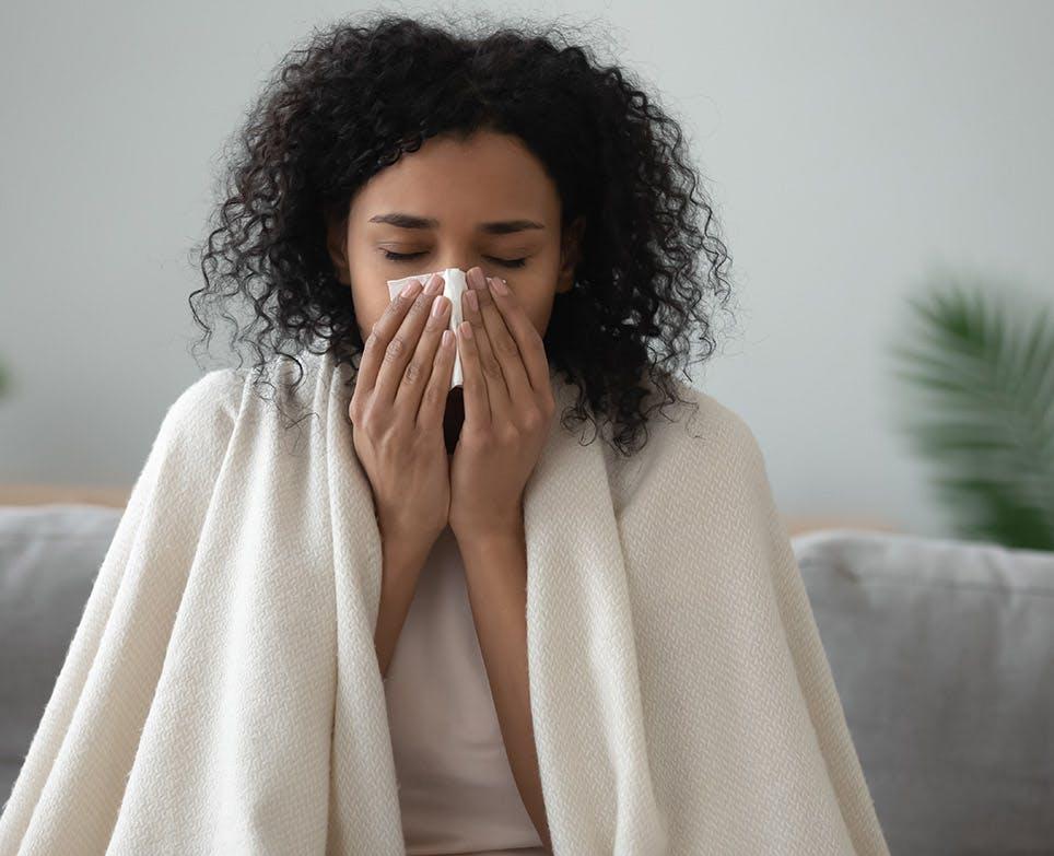 Mujer con congestión nasal, limpiando su nariz.