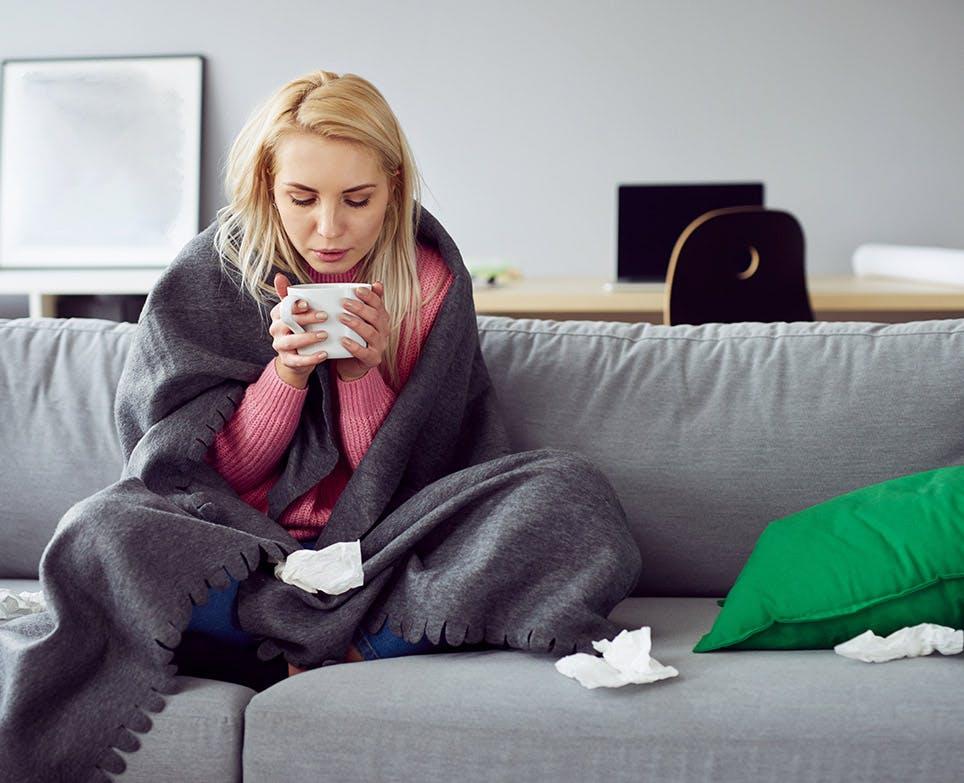 Mujer con síntomas de resfriado, tomando una bebida caliente.