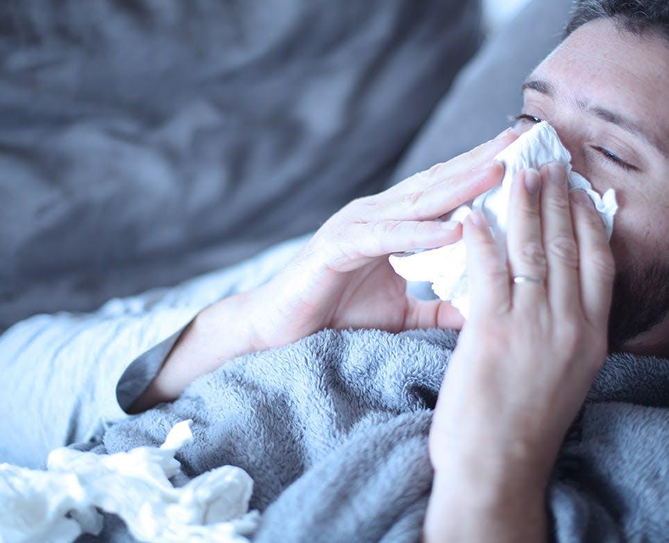 Hombre con congestión nasal, limpiando su nariz.
