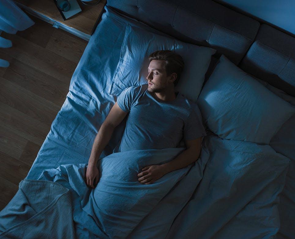 Hombre joven descansando en su cama.