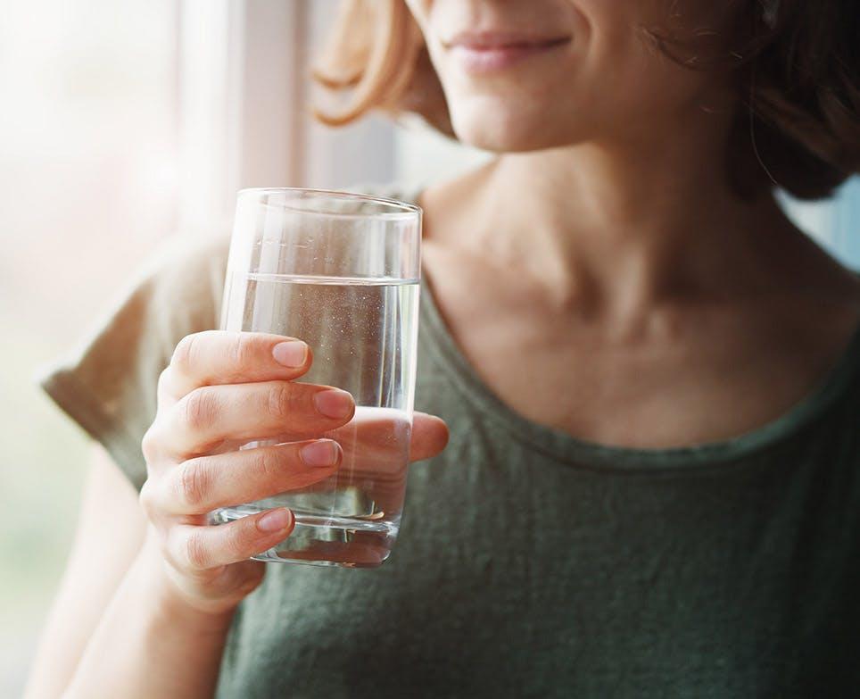 Mujer sosteniendo un vaso de agua.