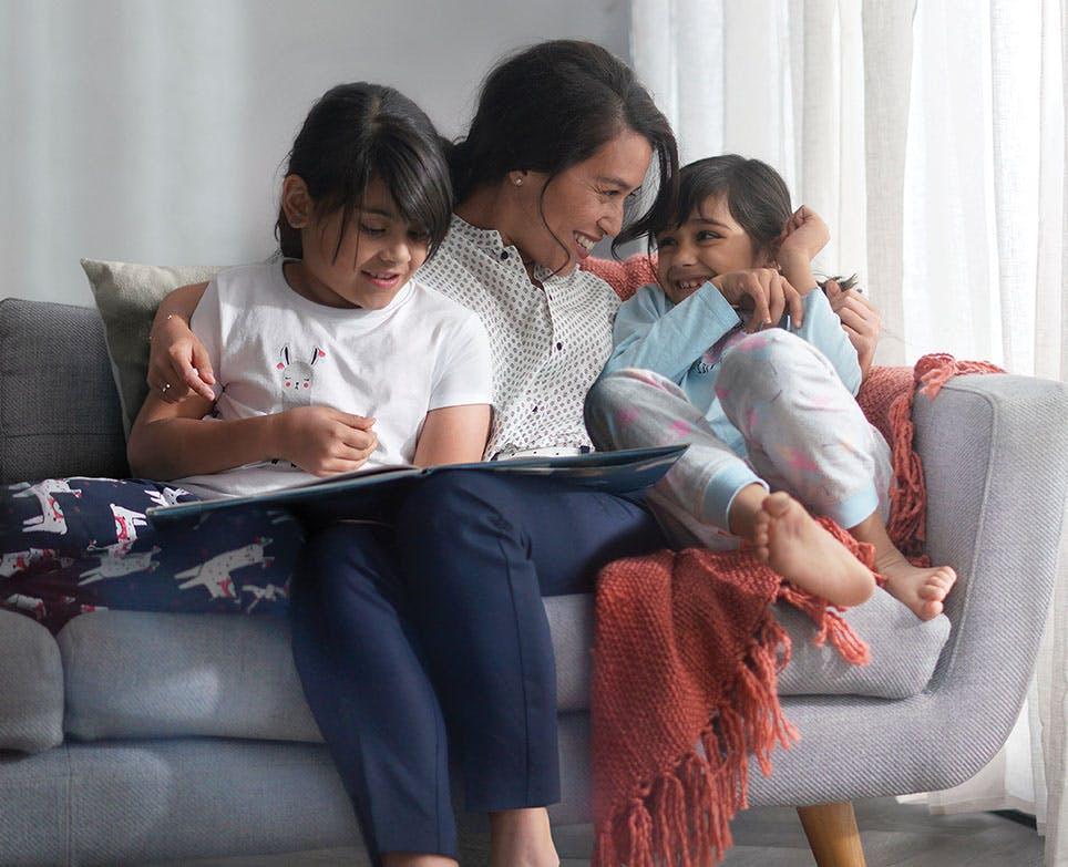 Madre con sus dos hijas leyendo un libro