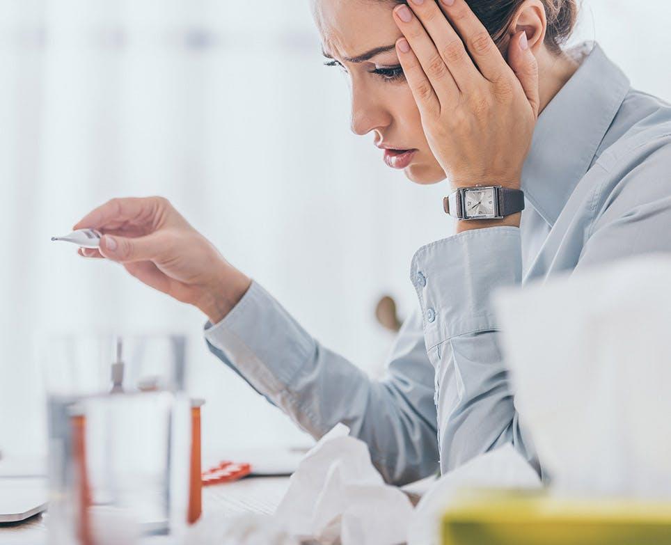 Mujer tomandose la cabeza mientras hace lectura de temperatura en termómetro.
