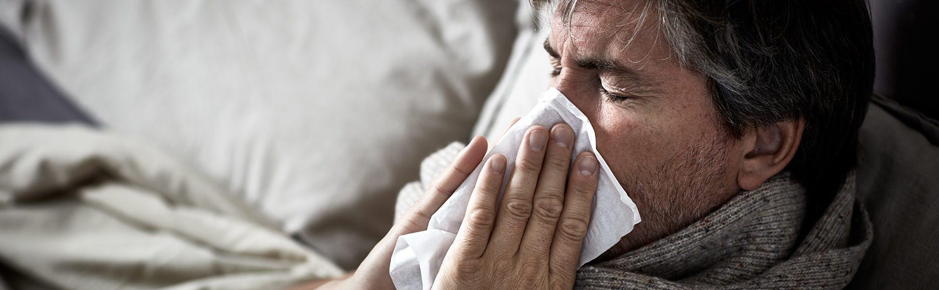Hombre con congestión nasal limpiando su nariz.