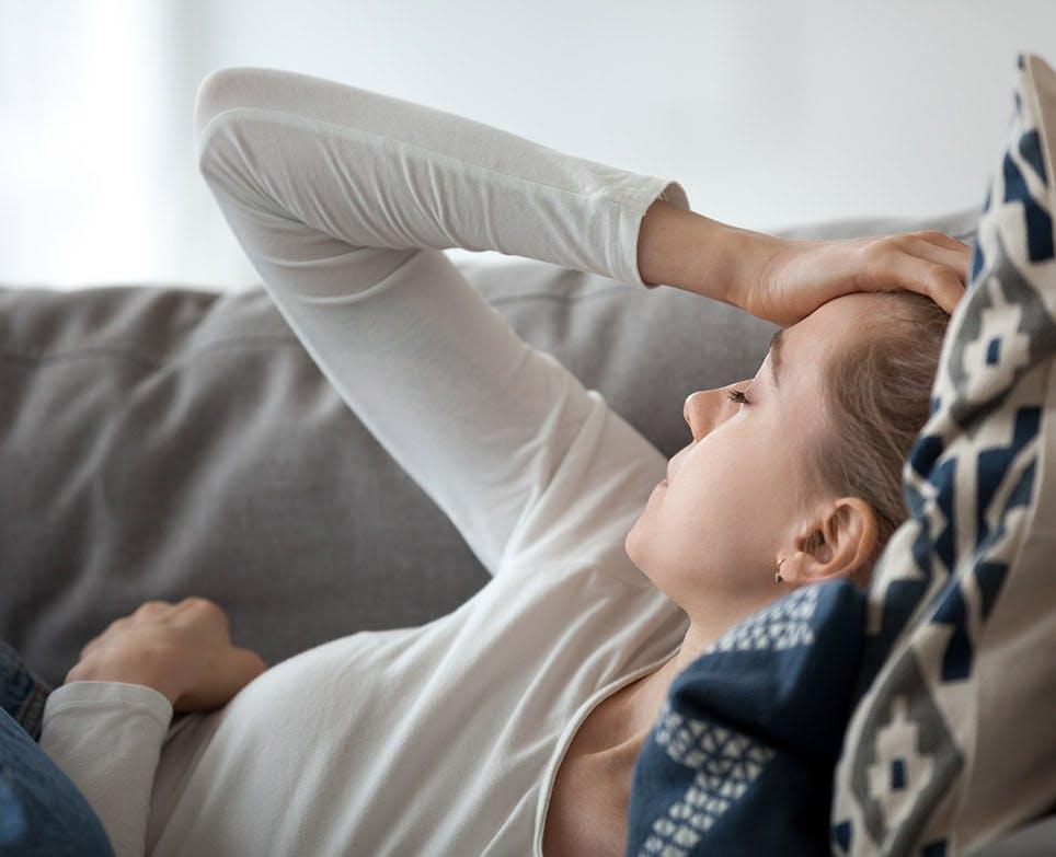 Representación de dolor de cabeza en una mujer joven, recostada, mientras se toca la cabeza