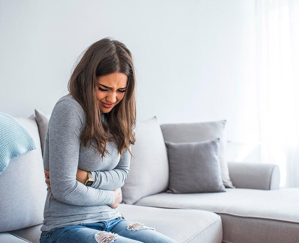 Mujer sentada en un sillón con señales de dolor en el vientre bajo.