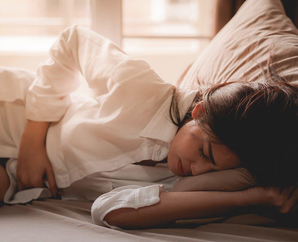 Mujer recostada en la cama tocándose el vientre bajo con la mano derecha en señal de dolor.