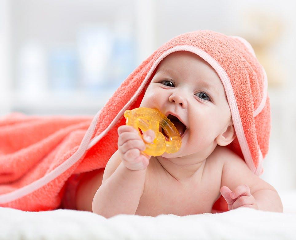 Bebé metiéndose un muñeco a la boca.