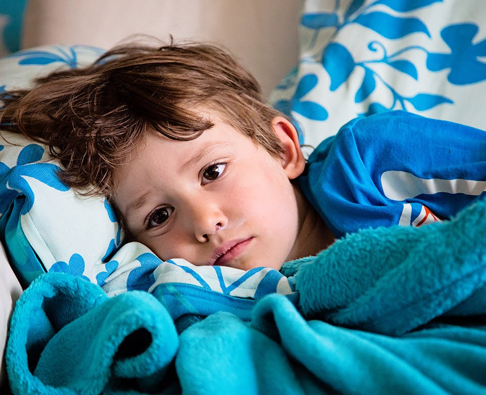 Niño recostado en su cama con síntomas gripales.