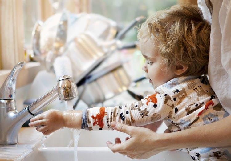 Barn får hjælp til at vaske hænder