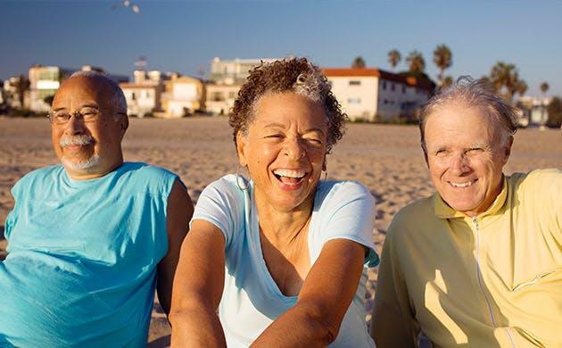 Tre ældre venner slapper af på stranden