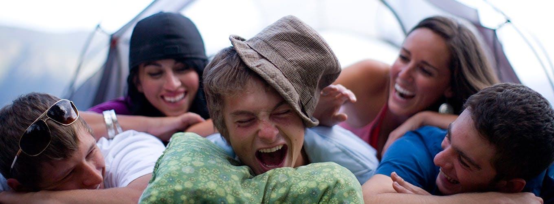 Venner griner, mens de er på telttur