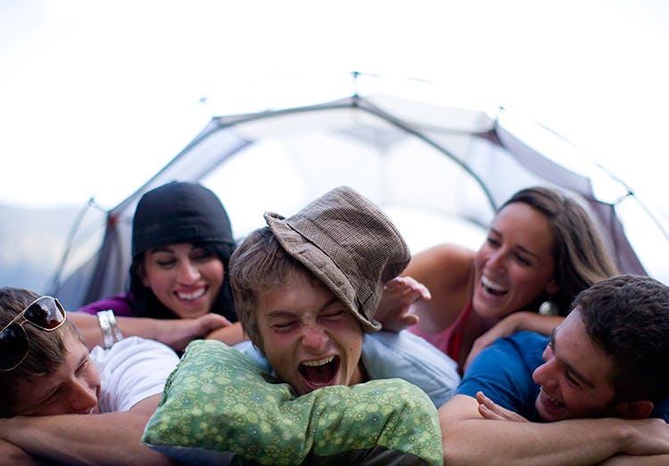 Stressfrie unge mennesker ligger sammen i telt og ler
