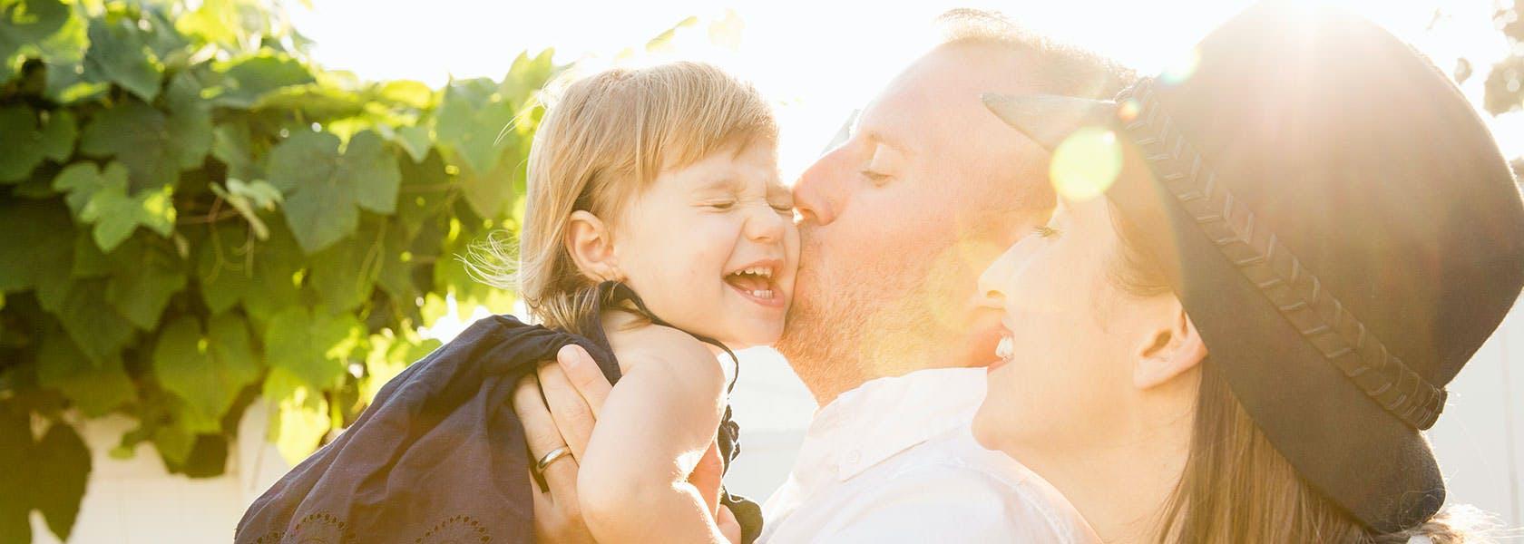 Forældre kysser og kæler deres datter