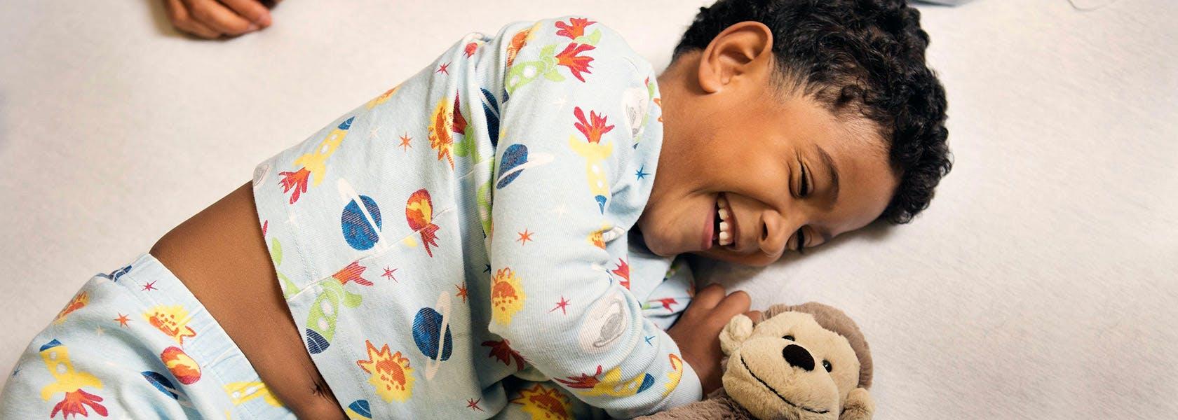 Dreng ligger med sin bamse og ler