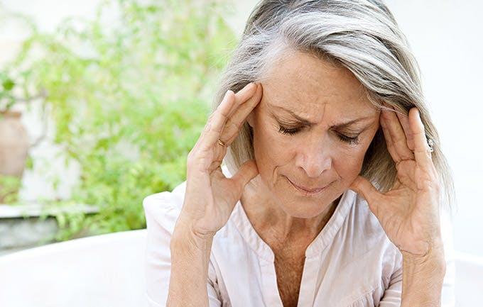 Ældre kvinde har hovedpine og holder om sit hoved
