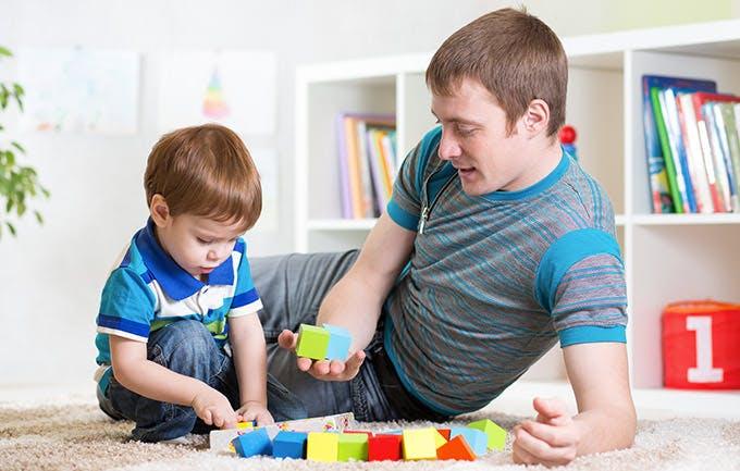 Far og søn leger med brikker