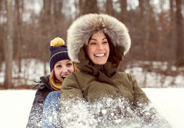 Mor og datter kælker sammen i sneen