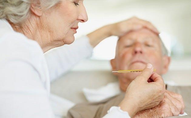 Ældre kvinde kontrollerer sin mands feber