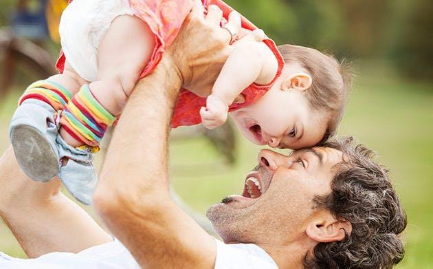 En far leger med sin datter i en park