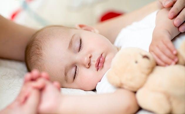 Baby sover trygt og bliver holdt i hånden