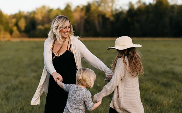 Mother Dancing With Her Daughters In A Field