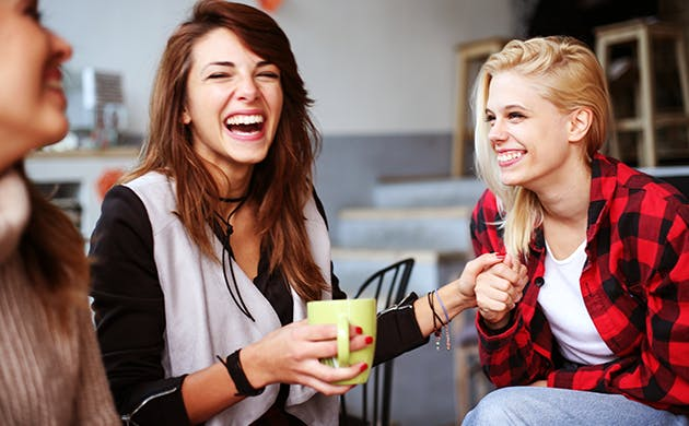 Tres amigas comparten y ríen.