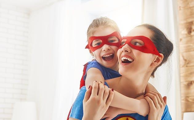 Una mamá y su hija se abrazan disfrazadas de super heroínas.