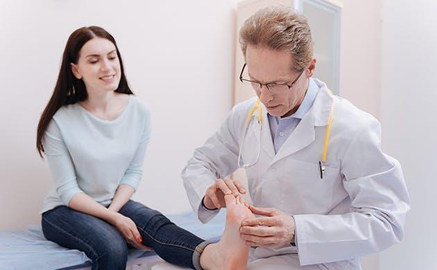 Medico revisandole la planta del pie a una mujer.