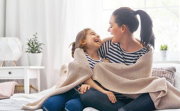 Una mamá y su hija abrazadas y cubiertas por una cobija.