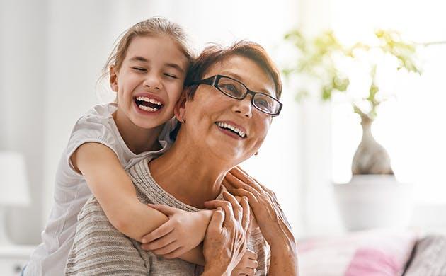 Una niña abraza a una mujer por la espalda, las dos sonríen.