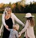 Una mamá juega con sus dos hijas al aire libre.