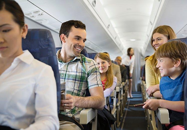 Familia sonriendo en un avión.