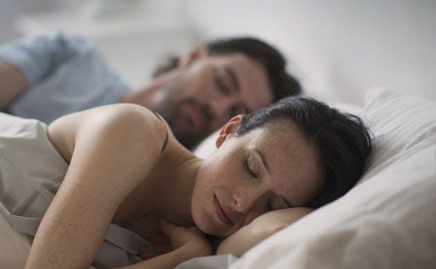 Una pareja de esposos duermen en la cama.