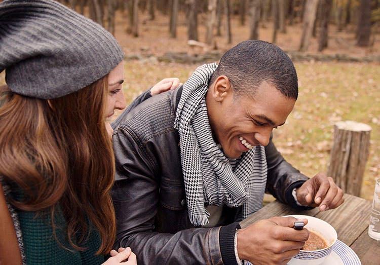 Mujer sonríe con su pareja mientras almuerzan al aire libre.