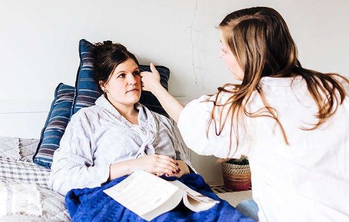 Una médico toca la cara de una paciente mujer que descansa en su cama.