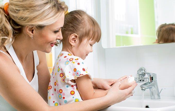 Una mamá le ayuda a su hija a lavarse las manos.
