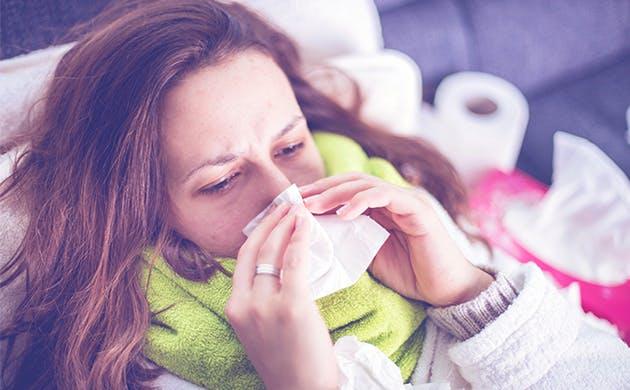 Mujer con síntomas gripales se suena.