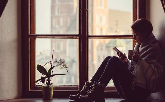 Una mujer joven senatada junto a un ventanal toma una bebida caliente mientras revisa su celular.