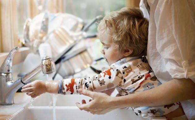 Mãe ajuda filho a lavar as mãos