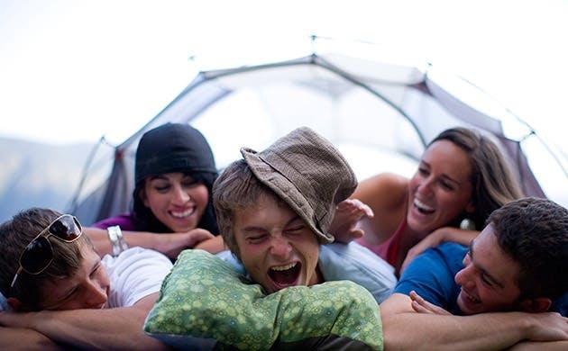 Amigos divertem-se a acampar