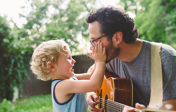 Pai toca guitarra para o seu filho
