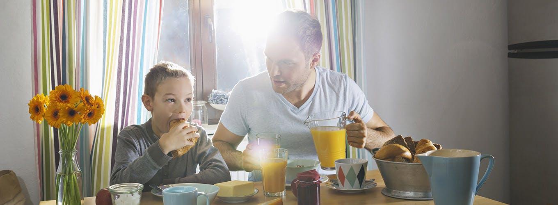 Cha và con ngồi ăn sáng ở bàn ăn