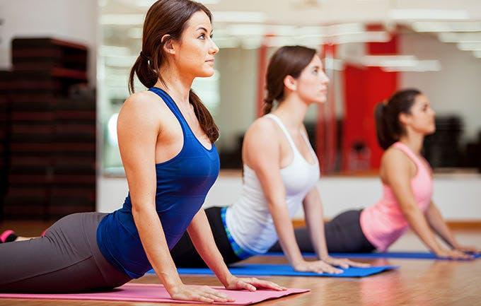 Phụ nữ luyện tập tư thể rắn hổ mang tại lớp học yoga