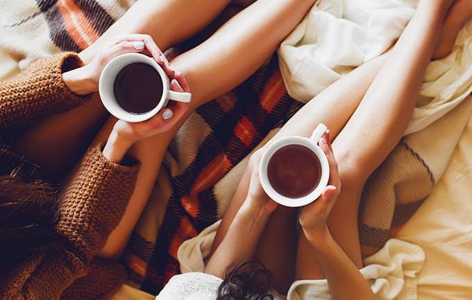 Hai chị em trong phòng ngủ cùng sách cũ và tách cà phê trên tay, mặc áo len ấm